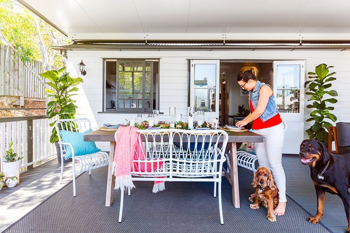 A rug defines the alfresco dining area. White plastic chairs from Kmart.