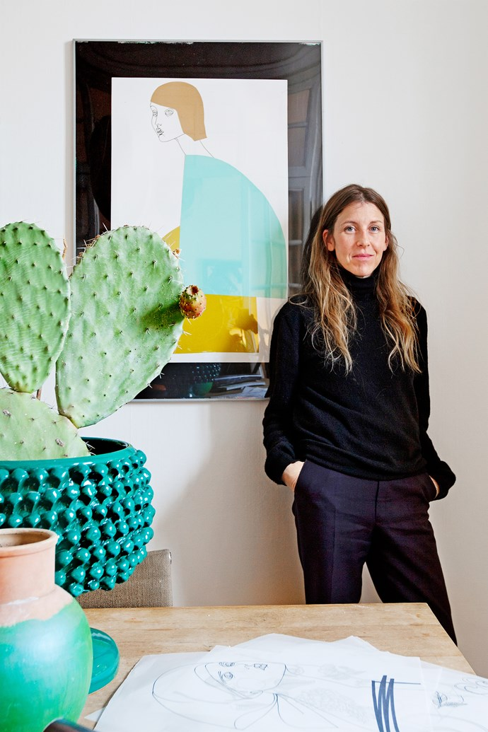 Liselotte stands in front of one of her illustrations. Cactus cuttings make a statement in a retro turquoise vase.