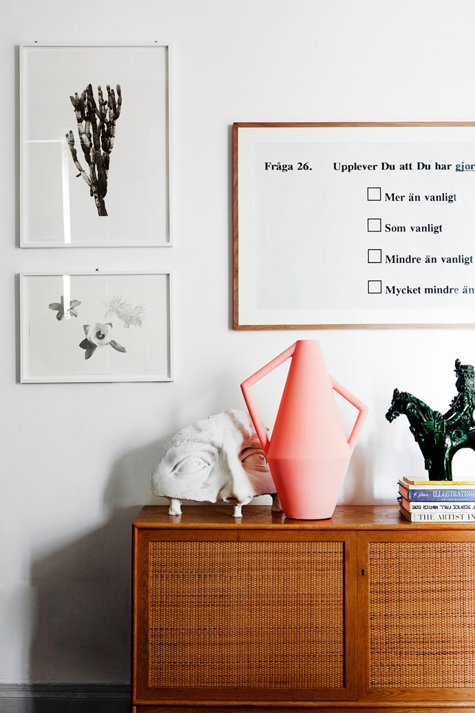 Quirky items such as a half-face cast and horse statue liven up the sideboard, as does an angular pink vessel.