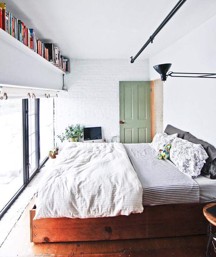 The bedroom is small but the white palette, lack of clutter and simple roll-up blinds keep the look simple. A black work lamp is angled upward for softer lighting above the bed.