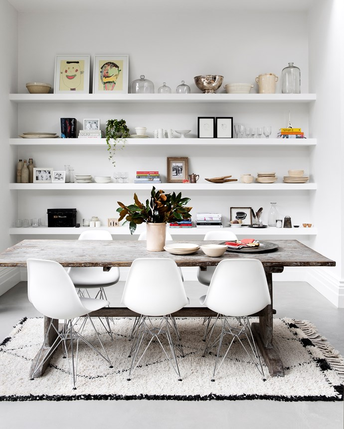 """""""The open shelves are constantly changing,"""" says Susanne, who loves to rotate displays. Antique table and vintage rug."""