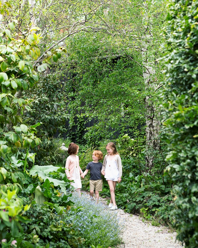 With a pebbled path meandering through dense plantings, the rear garden has an enchanting quality that twins Alice (left) and May, as well as young Barnaby, love.