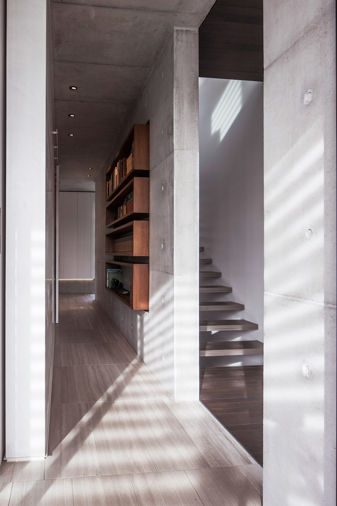 Timber floating stairs and off-form concrete blade walls.