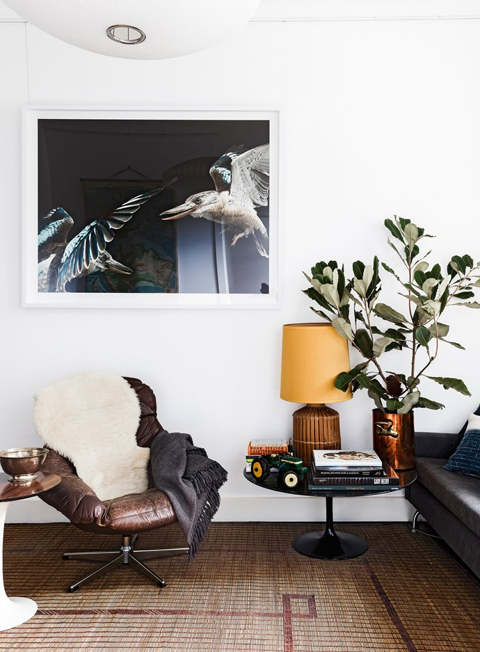 An image of kingfishers by Gary Heery floats above a vintage leather swivel chair and Eero Saarinen coffee table.