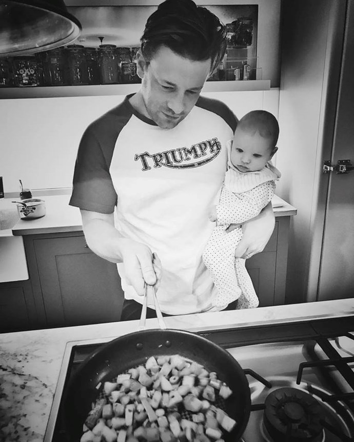 """Jamie Oliver is teaching baby River the ropes in this adorable snap posted on his Facebook. Captioning the sweet image """"Gotta start them young!..... bless baby River he's so fascinated by the cooking,"""" we wonder if River has a future job lined up for him in dad's kitchen."""