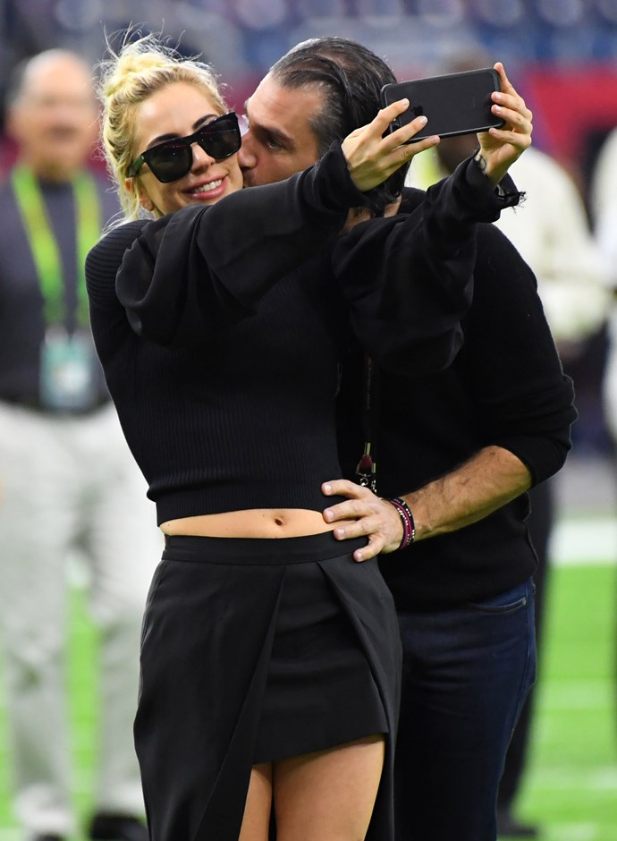 Lady Gaga and Christian cosied up on the field before the Super Bowl.