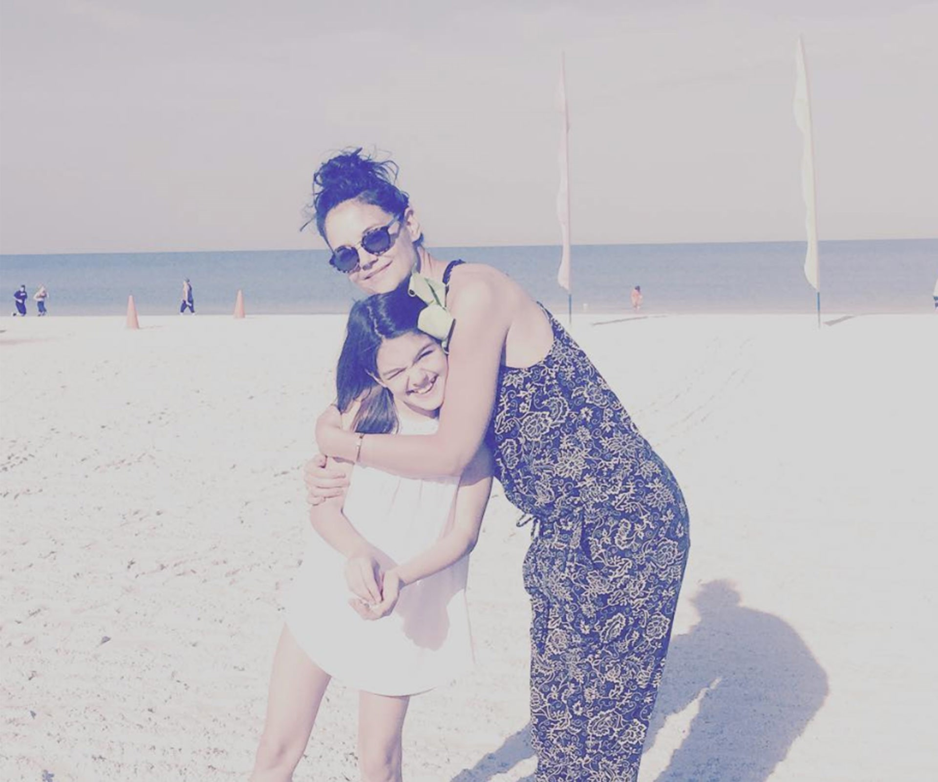 "Katie Holmes and her look-alike daughter Suri Cruise are making us miss the summer sun with their adorable getaway snaps. ""My sweetie,"" the actress wrote beside this adorable beach memory."