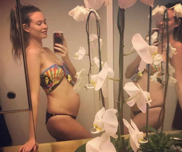 """The supermodel is known for her fun-loving attitude and laid-back style, so it's no surprise that when Behati, 28, decided to announce her and rockstar Adam Levine's baby news, her approach was perfectly casual. The South African-Namibian beauty took to Instagram to post a mirror selfie in a mis-matched bikini, her long locks swept into a pony, showing an obvious baby bump. """"ROUND 2..."""" she captioned the shot."""
