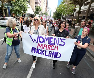 Lizzie Marvelly (in white sleeveless top) walks behind broadcaster Ali Mau (at front in sunglasses) along Auckland's Queen Street on January 21, in a global show of solidarity with those marching in Washington DC.
