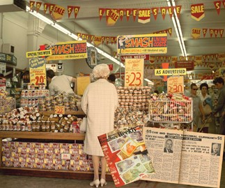 An elderly woman looks over some  of the bargain items in a grocery store in Auckland, 1968.