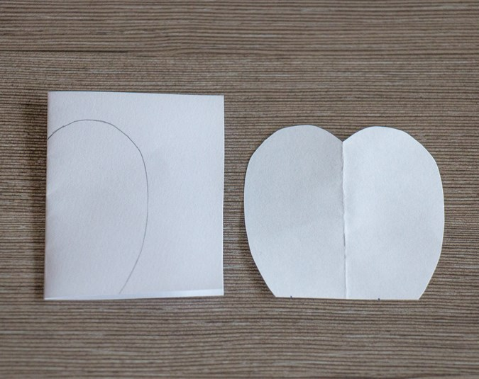 1. Fold a small piece of paper in half and draw a half petal shape on one side. Mine was 5cm high and 3cm wide. Cut it out and open it up.