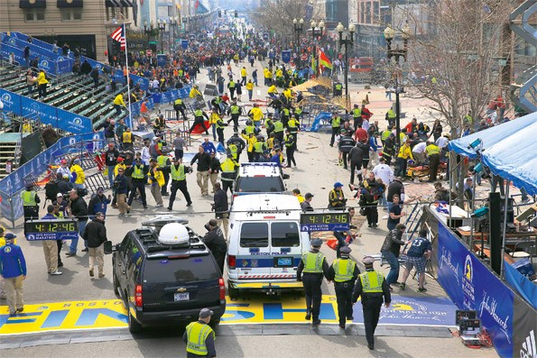 Emergency personnel respond to the scene after two explosions went off near the finish line of the 117th Boston Marathon. (Photo by David L. RyanThe Boston Globe via Getty Images)