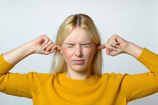 Woman blocking her ears