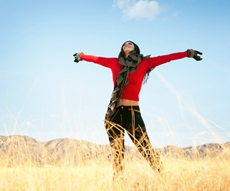 Woman in field, happy, arms outstretched
