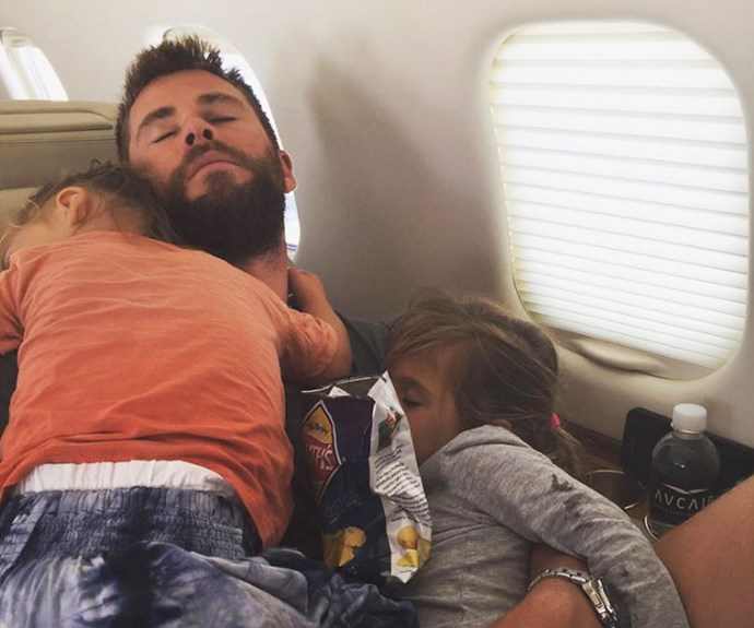 """Proud mama Elsa Pataky posted this sweet snap of husband Chris Hemsworth napping in an airplane seat with his four-year-old daughter India Rose and one of his two-year-old twin sons. """"Nothing better than sleeping in papa's arms!"""" She captioned the memorable moment."""
