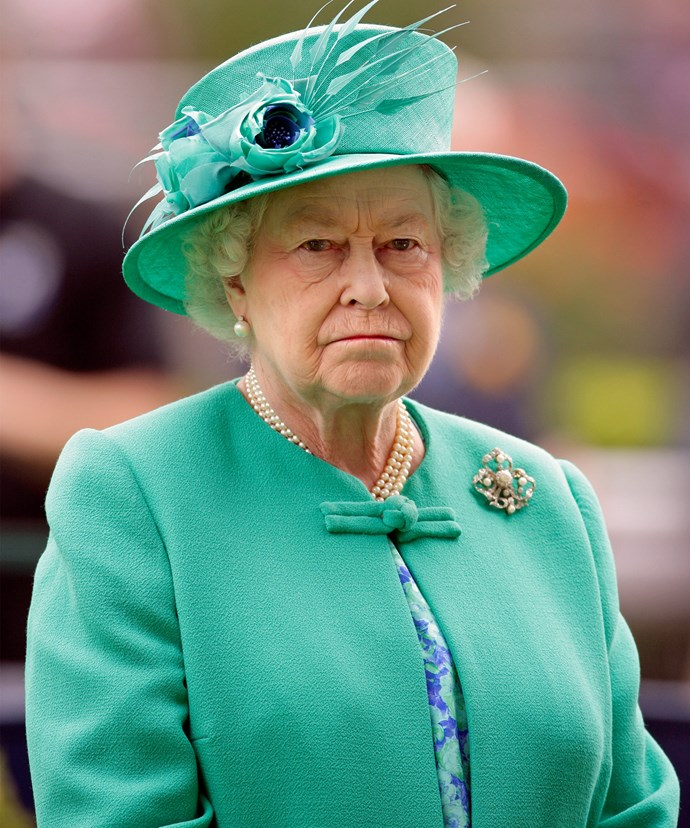 Although the Queen looks stern here, her love for bright colours shows with this teal jacket and matching hat.
