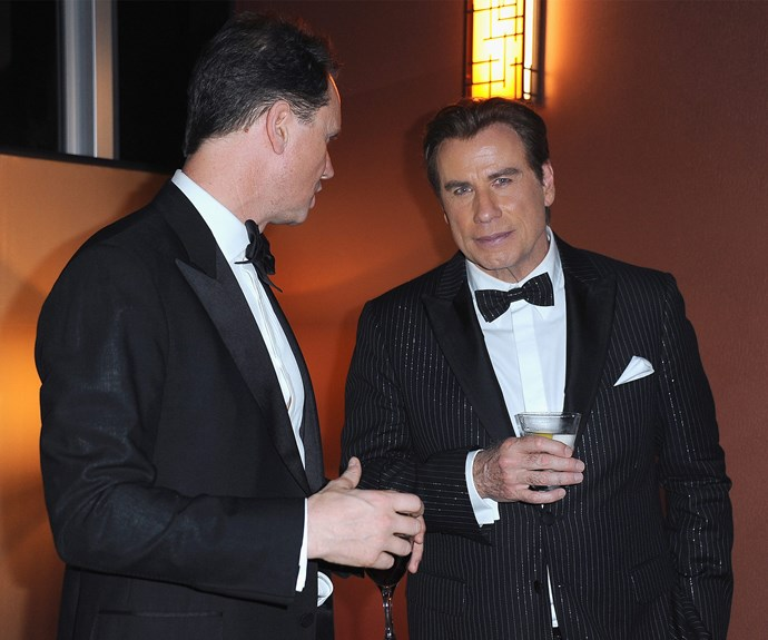 John Travolta looks to be deep in conversation.