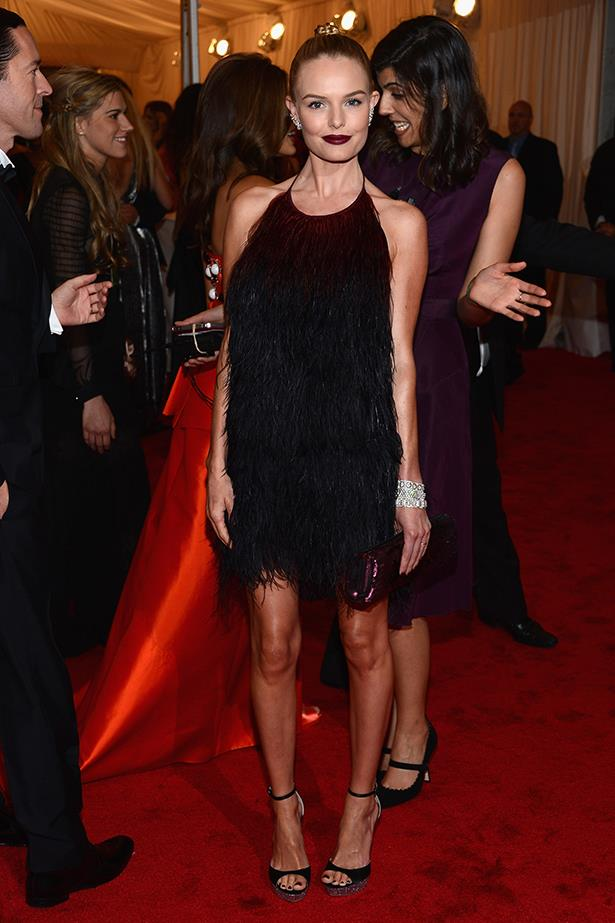 Bossy plays the (loveable) vixen at the 2012 Met Gala in a dangerously feathered Prada mini, killer Miu Miu pumps and a to-die-for plum pout.