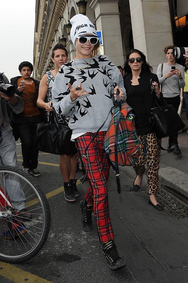Fashion's wild child Cara Delevingne dons her usual mismatched attire and slogan beanie during an outing at Paris Fashion Week.