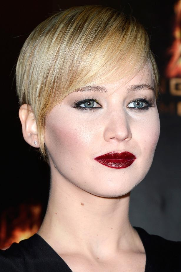 J-Law goes gothic with a dark lip, porcelain skin and a glittered smoky eye. Her short blonde 'do is styled in a heavy side sweep.
