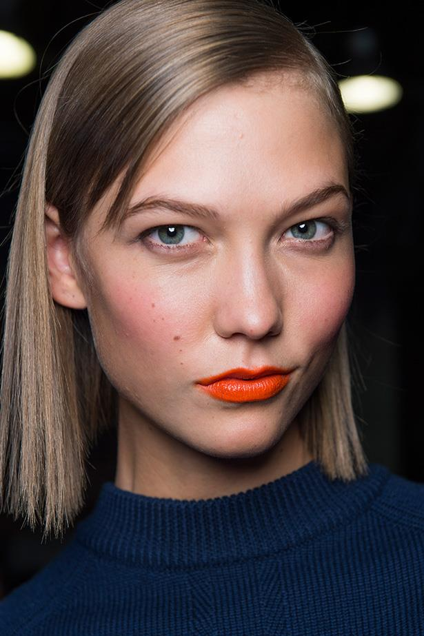 Go for a bright pop of colour with orange lipstick—it instantly makes anyone look tanned and glowing— and is helped along by a touch of peachy blusher.