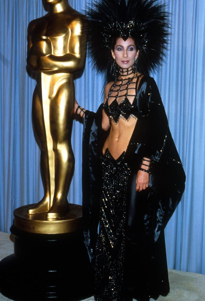 <strong>Cher, 1986</strong><br></br> Renowned for her bold and eccentric fashion choices, Cher didn't disappoint in 1986 when she donned this provocative Bob Mackie get-up to present the award for Best Supporting Actor. The Mohawk-style headpiece was made from hundreds of rooster feathers and she reportedly had to sit on the floor of the limo to fit it in!