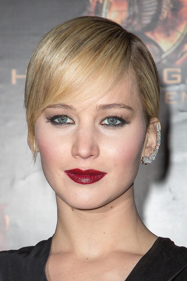 Jennifer Lawrence styles her heavily encrusted ear cuff with a dark plum lip.