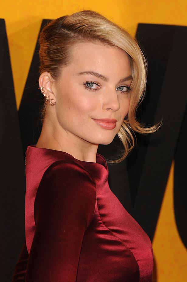 Australian actress Margot Robbie showcases her ear cuff with a slick 'do and satin dress.