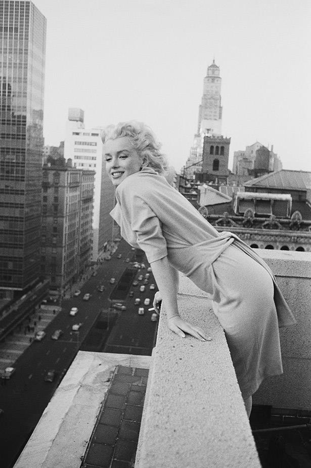 1955, a fresh-faced Marilyn Monroe leans over the balcony of the Ambassador Hotel in New York City.