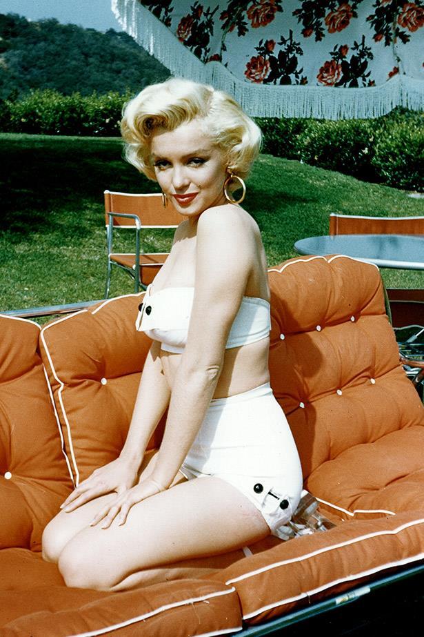 Marilyn the retro bombshell: Monroe poses on a garden settee in 1953.