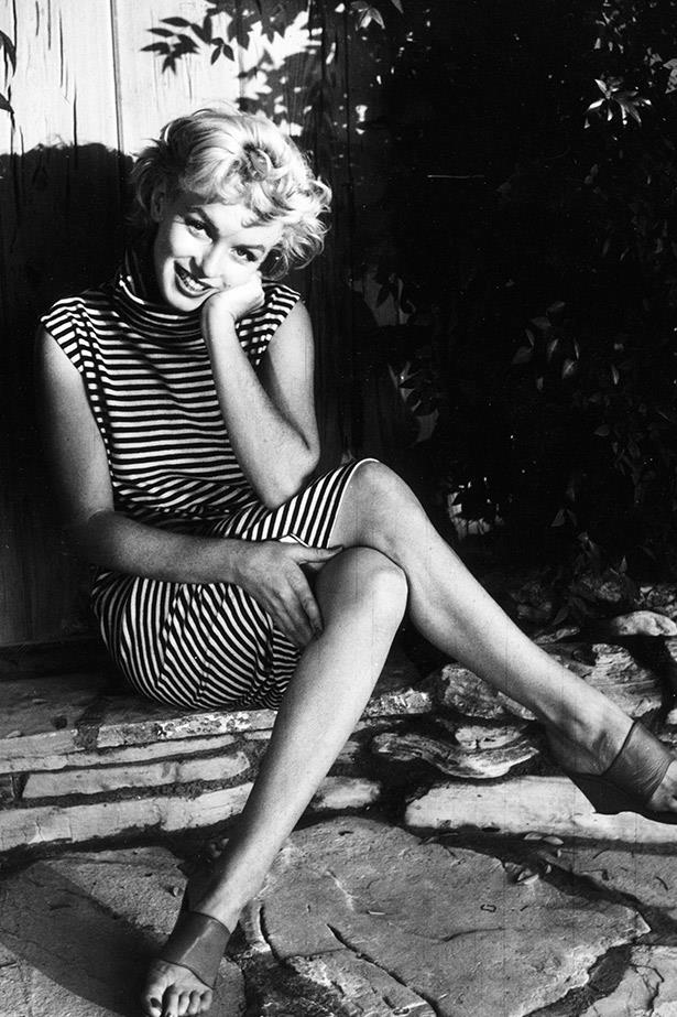 Marilyn Monroe glows in a timeless striped dress and sandals in a garden in 1954.