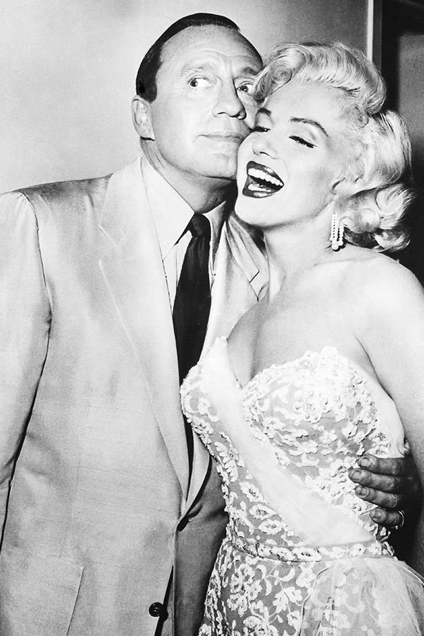 Wearing a beautiful embroidered strapless dress, Marilyn charms actor Jack Benny, circa mid-'50s.