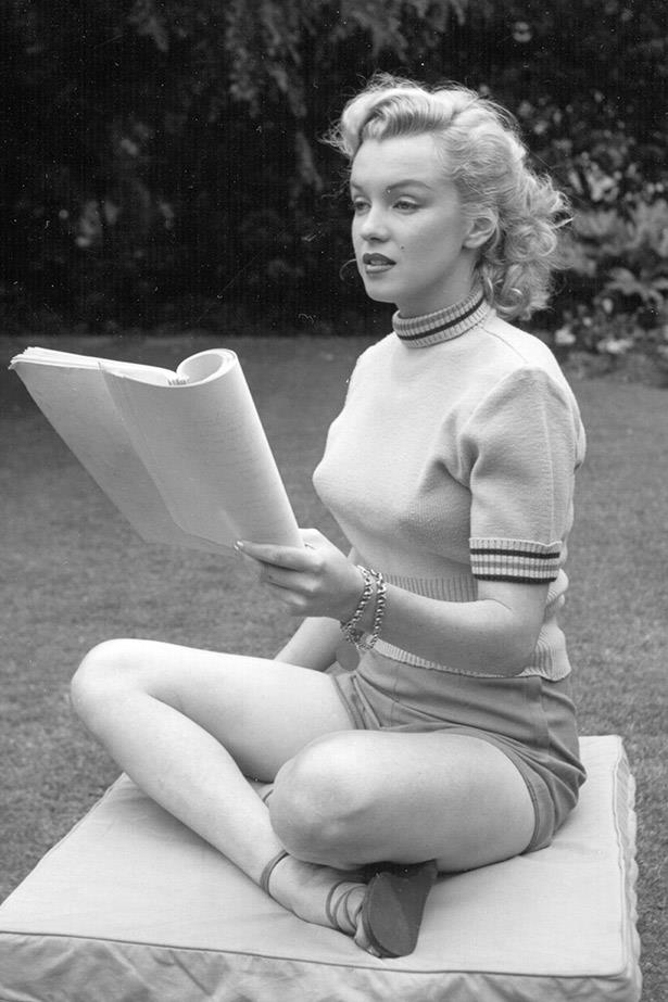 Marilyn Monroe poses while reading a script in Hollywood agent Johnny Hyde's backyard, 1950.