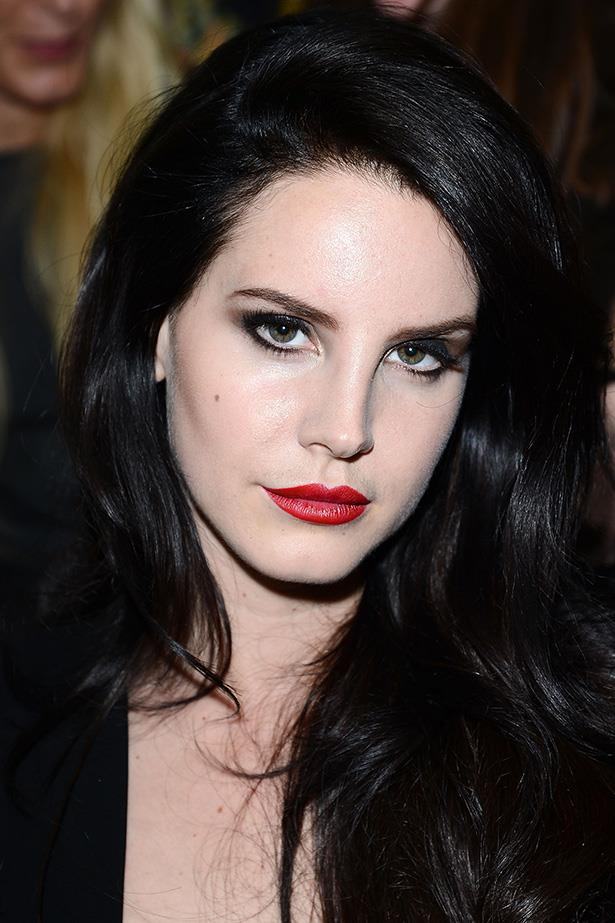 The New York native highlights her flawless porcelain complexion with deep brunette locks and a bright red lip front row at the Versace show in 2013.