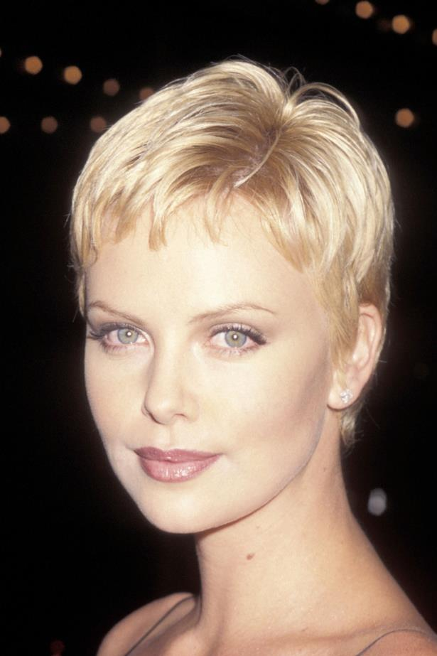 A fresh faced 22 year old Charlize is the epitome of 90's fashion with a slip dress and bleached blonde pixie-cut.