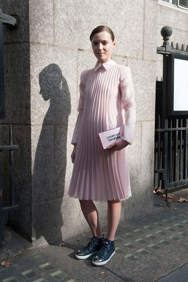 This look is the epitome of modern-day femininity with a sheer pink pleated dress, Miu Miu glitter sneakers and a slogan clutch.