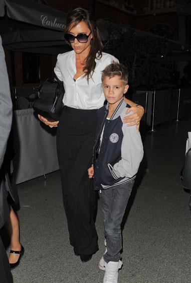 Victoria Beckham kept it monochrome on the streets of Paris with her son Romeo, wearing a Jil Sander skirt, Maison Martin Margiela shirt and a bag from her own label.