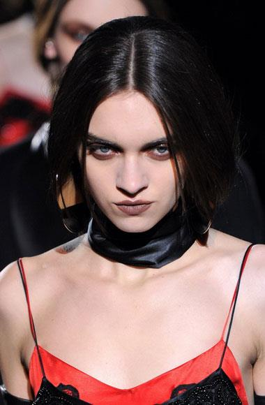 "The new gothic: ""It's the new goth. It's modern and it's chic,"" said hair stylist Luigi Morenu about the look that he and makeup artist Pat McGrath had created for Givenchy's moody A/W 12-13 collection. It was certainly new: a pallid complexion, a smoky eye on a deep gradient and a dark, matte lip. The look is one that was echoed at Jean Paul Gaultier, where kohl was applied to the models' lower eyelids with fingertips by Stephane Marais, or at Roberto Cavalli, where it was McGrath again who used undulating shades of wet-look metallic eyeshadows in amethyst and emerald green to create a modern-gothic aesthetic. Pictured: Givenchy A/W 2012-2013"