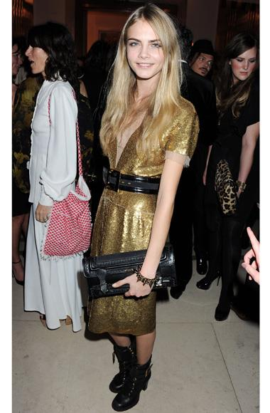 Burberry face Cara Delevingne adhered to the black and gold theme in a metallic Burberry dress.