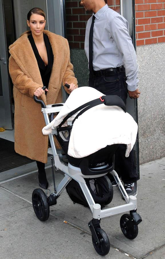 Wearing her favourite oversized Max Mara coat while out with baby North West on November 19, 2013.