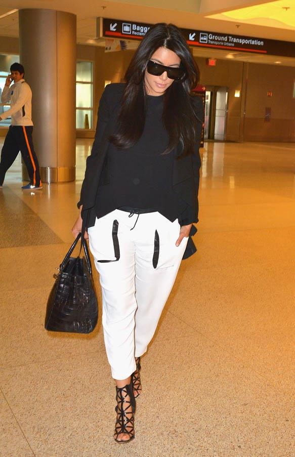 In her favourite travel uniform of black and white at Miami Airport in January 2013.