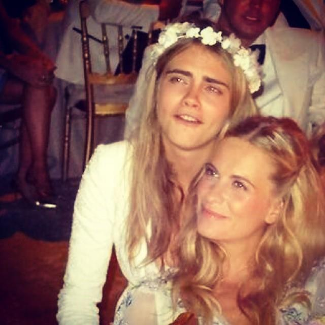 Cara wore a white dress with a flower headpiece, while Poppy wore her hair in loose, casual waves, pinned back at the front.
