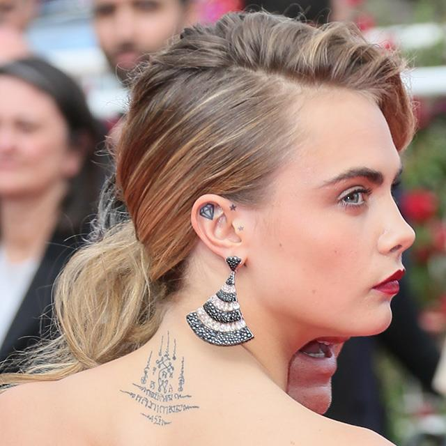 A close up of Delevingne's back and ear tattoos.