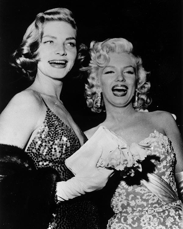 """In Hollywood, an equitable divorce settlement means each party getting fifty percent of publicity."" <br><br><em>Bacall with her ""How to Marry a Millionaire"" co-star Marilyn Monroe in 1954.</em>"