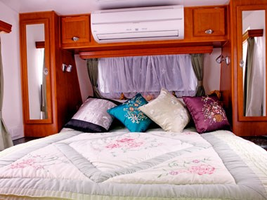 luxuriosu bed room in the Aussie By Design Humpback SmartVan Legend caravan