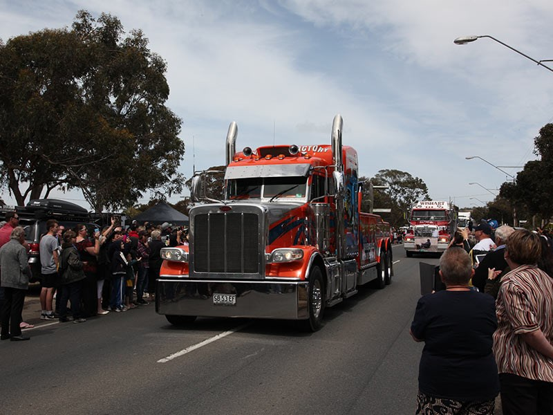 Trucks coming through White Hill past people assembled for the memorial service.