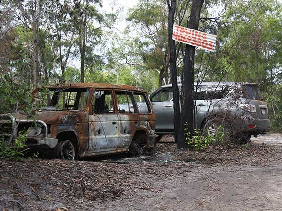 Nissan Patrol 4x4 with burnt-out vehicle