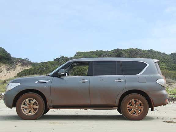 Side view of mud-covered Nissan Patrol 4x4