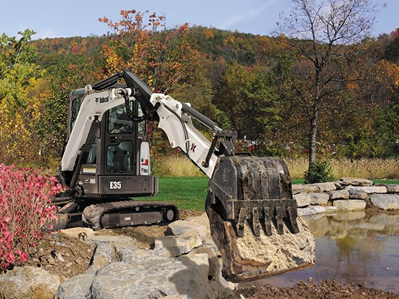 A Bobcat E35 compact excavator landscaping with an extended arm.