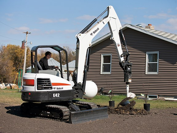 A Bobcat E42 compact excavator planting trees with an auger attachment.